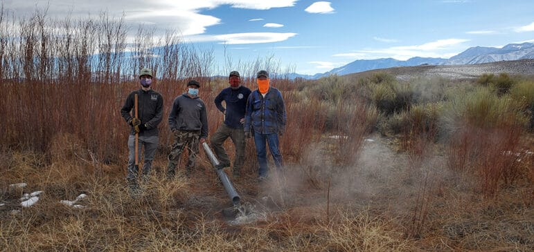 Four men in masks pose in the grasses near the pond with water flowing from a gray pipe on the ground.