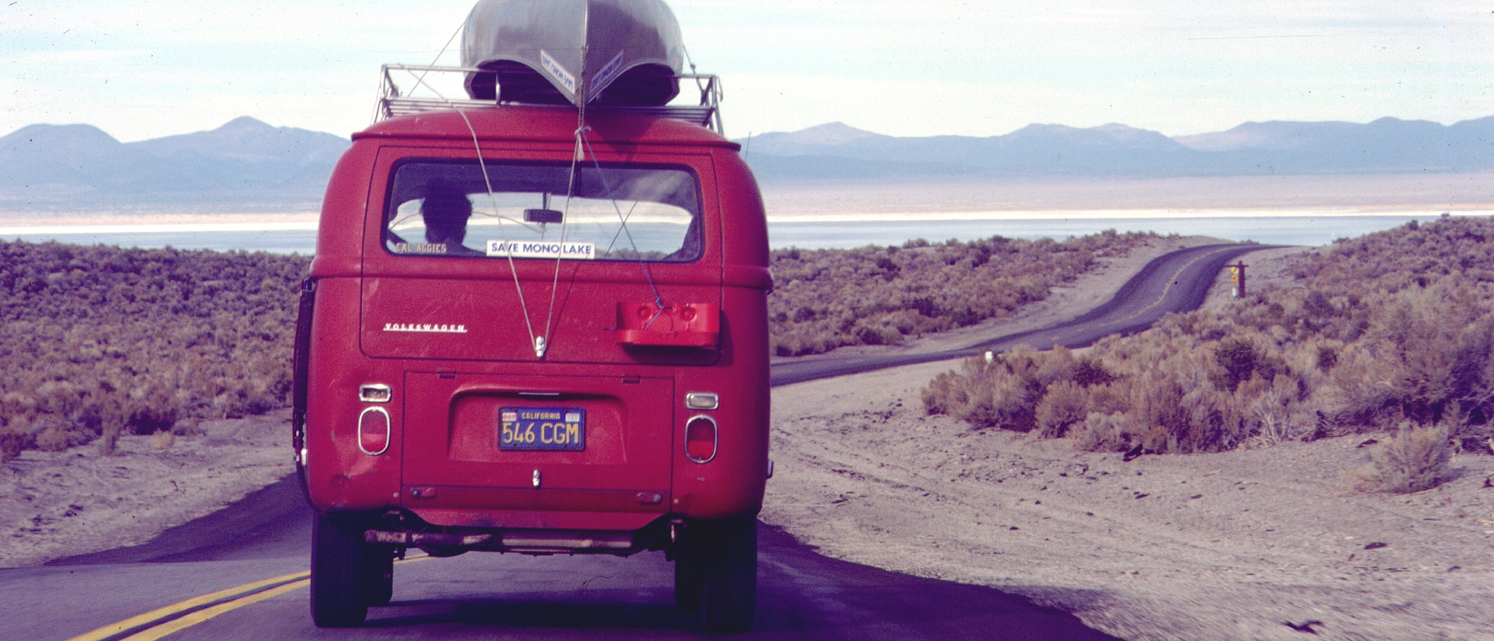 The back of a red bus with a canoe on the roof and a Mono Lake Sticker drives down the road towards the lake.