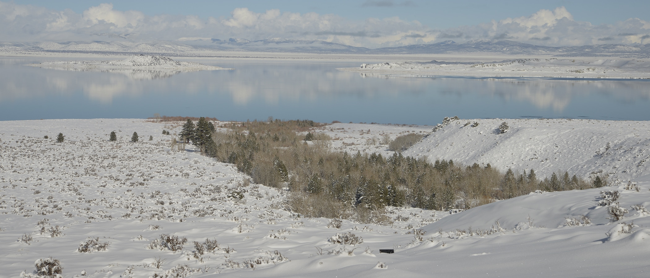 The islands on Mono Lake and surrounding mountains are covered in snow, and the still water reflects the light blue and cloudy sky above.