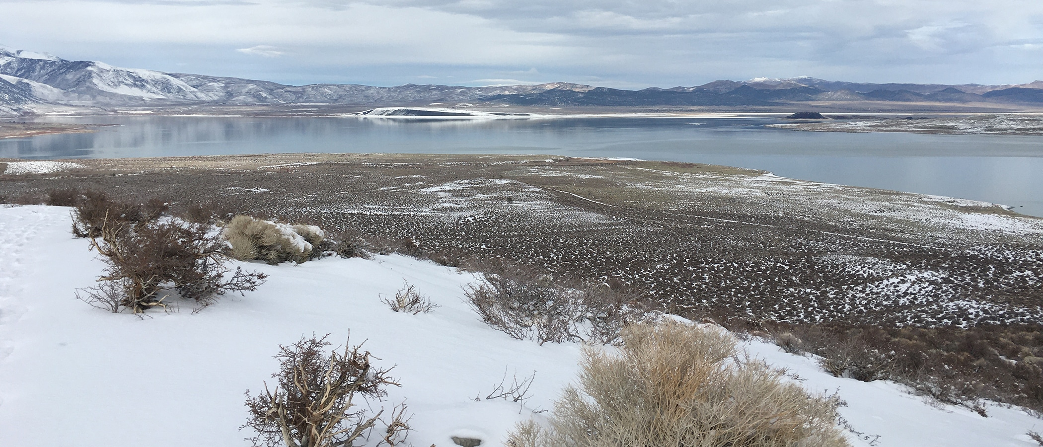 The view from Panum crater shows the snow speckled shore and the snow covered islands in the blue-gray Mono Lake water.