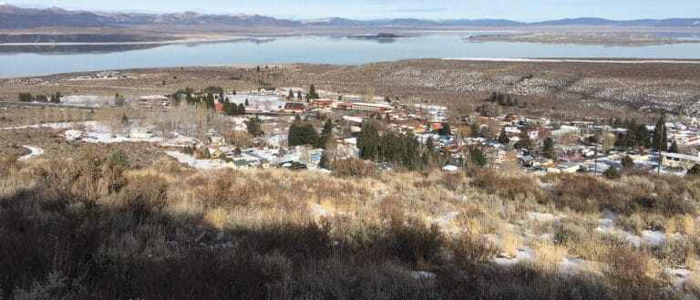 A birds eye view of Lee Vining buildings from a hill shows Mono Lake in the distance.
