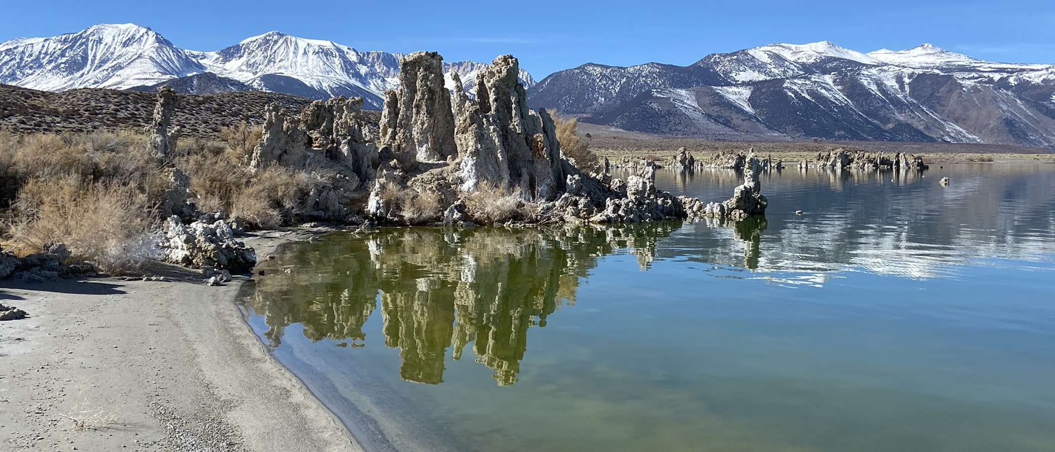 Tufa towers stand tall in turquoise Mono Lake water, with snowcapped Sierra Nevada mountains behind it.