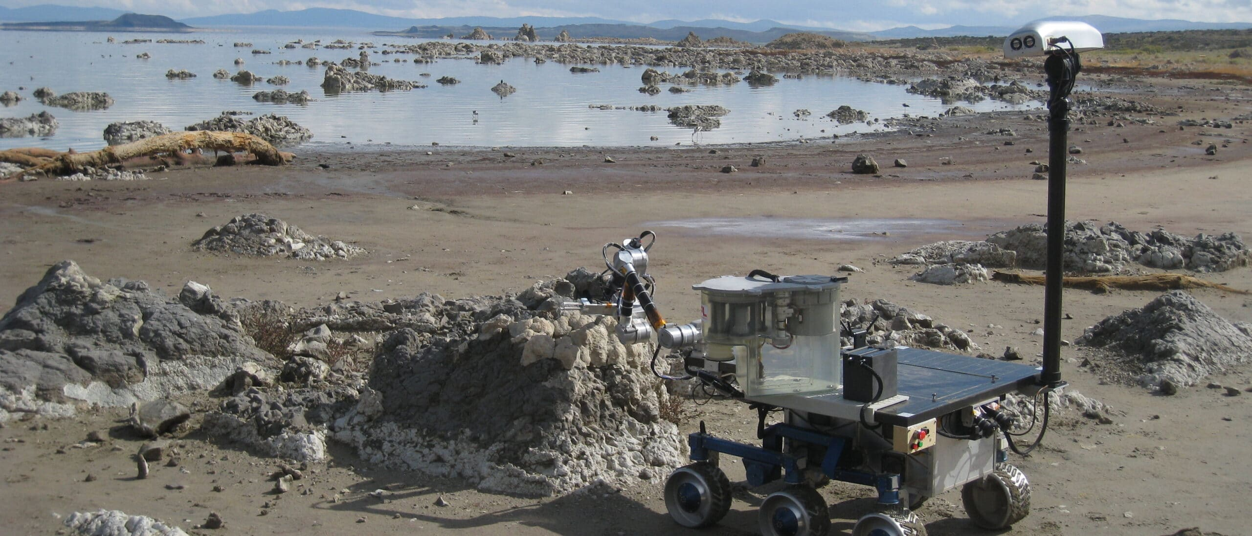 The mars rover, a metal machine with six wheels sits on the beach of Mono Lake near outcroppings of tufa.
