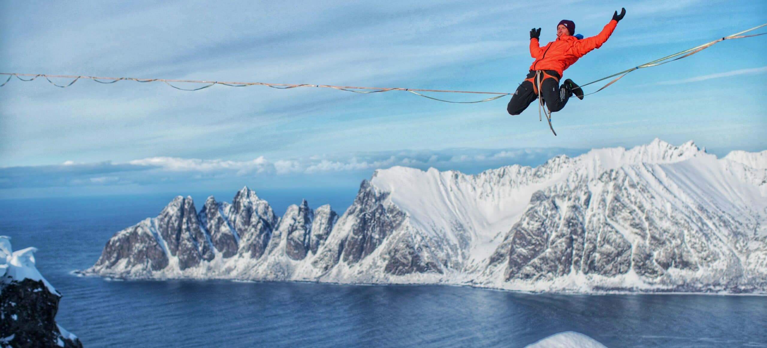 A man in an orange jacket sits on a tight rope with his hands outstretched. Huge snowy mountains and blue water loom below the high wire.