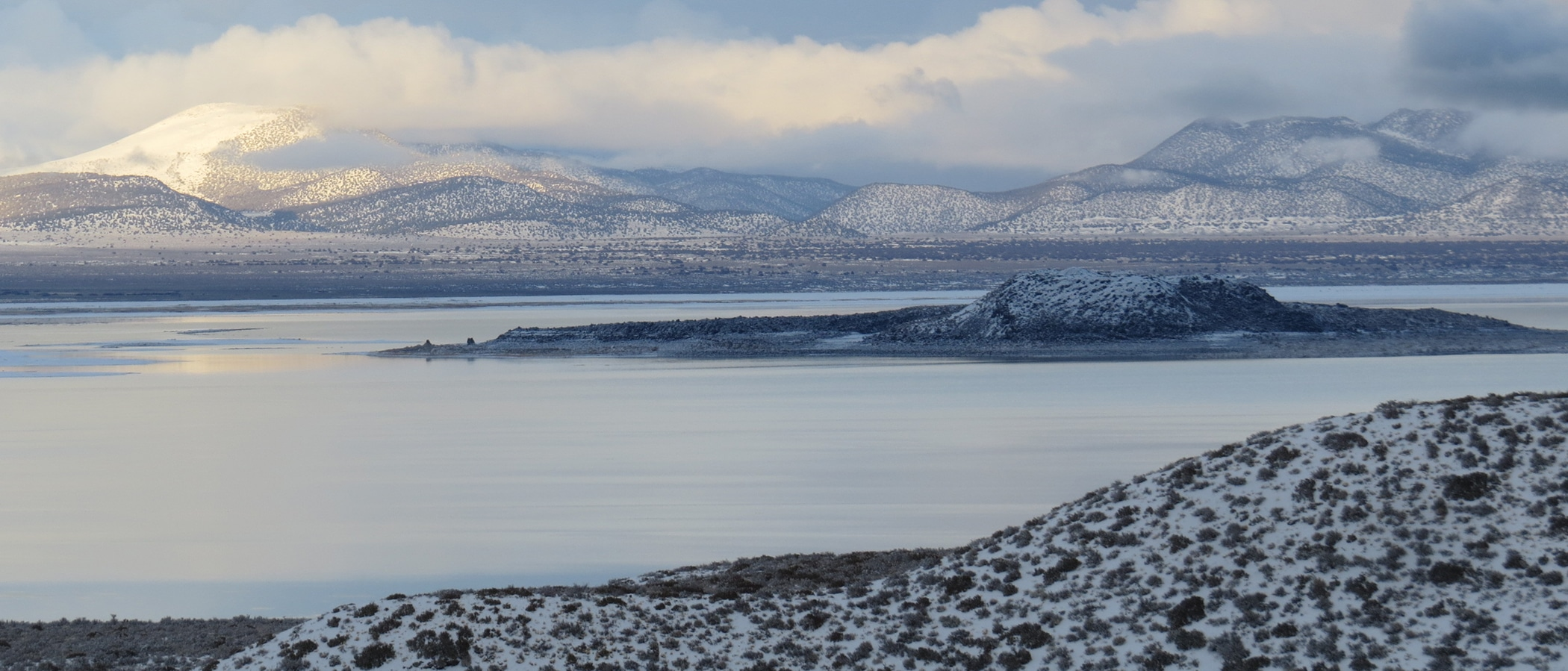 An island in Mono Lake is covered in snow, and so are the hilly mountains behind it. The sky is cloudy with yellow sunlight shining through onto the glassy light blue surface of the water.