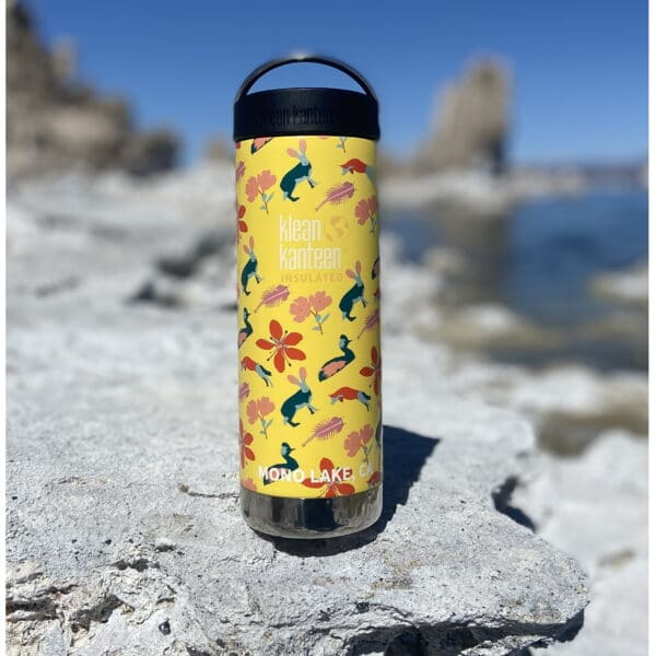 A yellow water bottle with flower and animal patterns sitting on tufa.