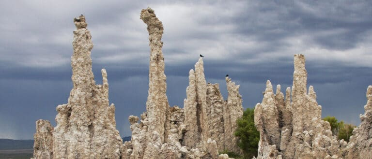 Tall, thin tufa towers reach into the gray-blue sky above.
