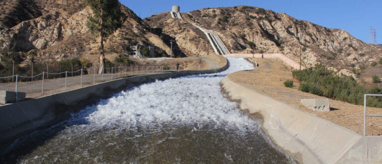 White water rushes down a cement trench from the top of a rocky brown hill.