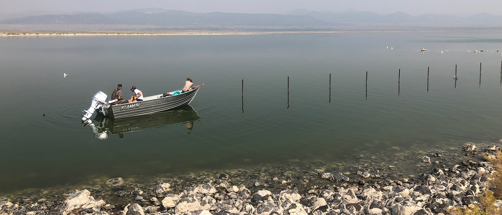 2 people sit in a small gray motor boat on the still, dark green water. On the right side of the boat, fence posts stick up out of the water.