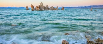 Turquoise Mono Lake water surface is rough with small waves, and tufa towers rise up in front of blue mountains and a pink and orange glowing sky.