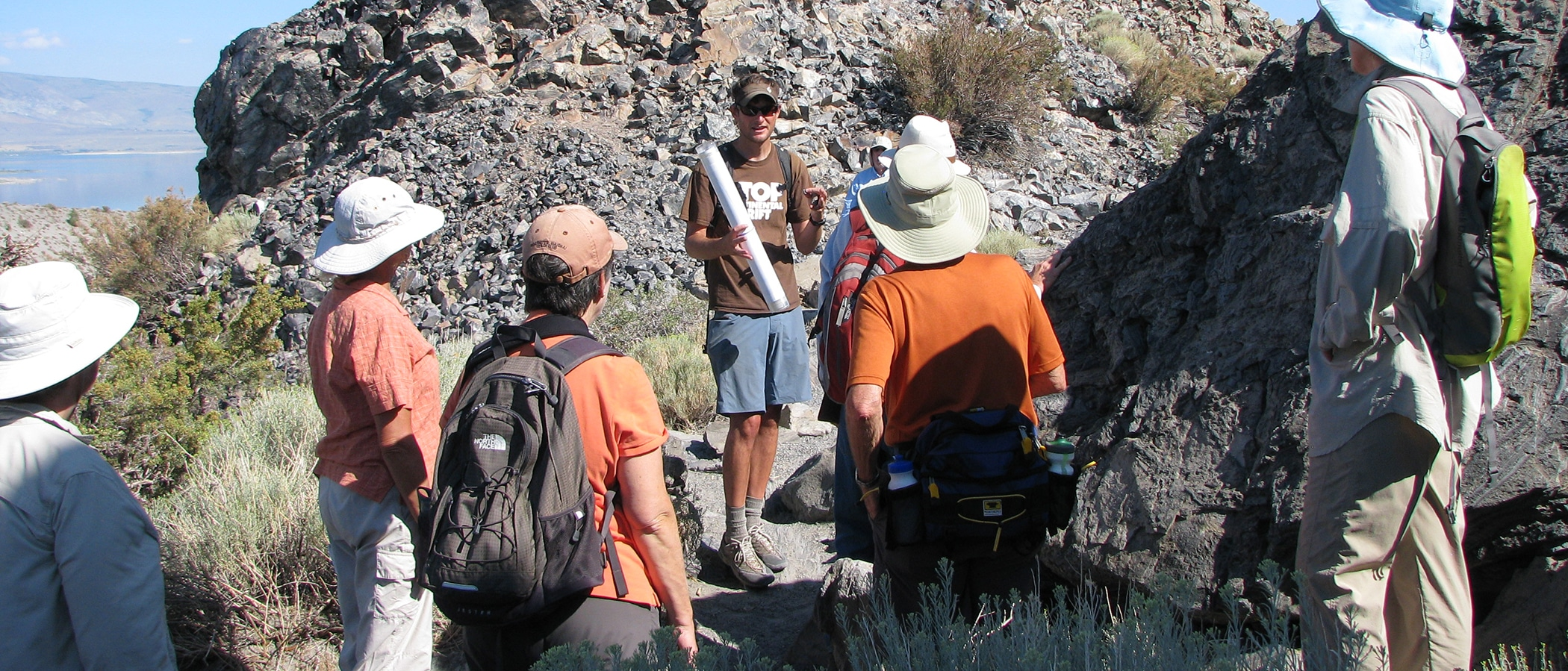 A man talks to a group in a rocky pathway.