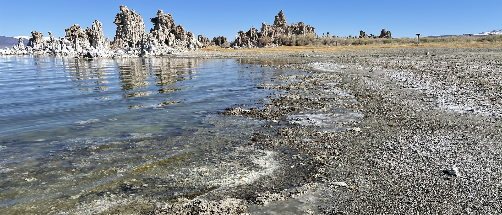 Mono Lake water reflects the blue sky, and water it frozen in bumpy puddles on top of the tufa beach. Tufa towers loom in the background.