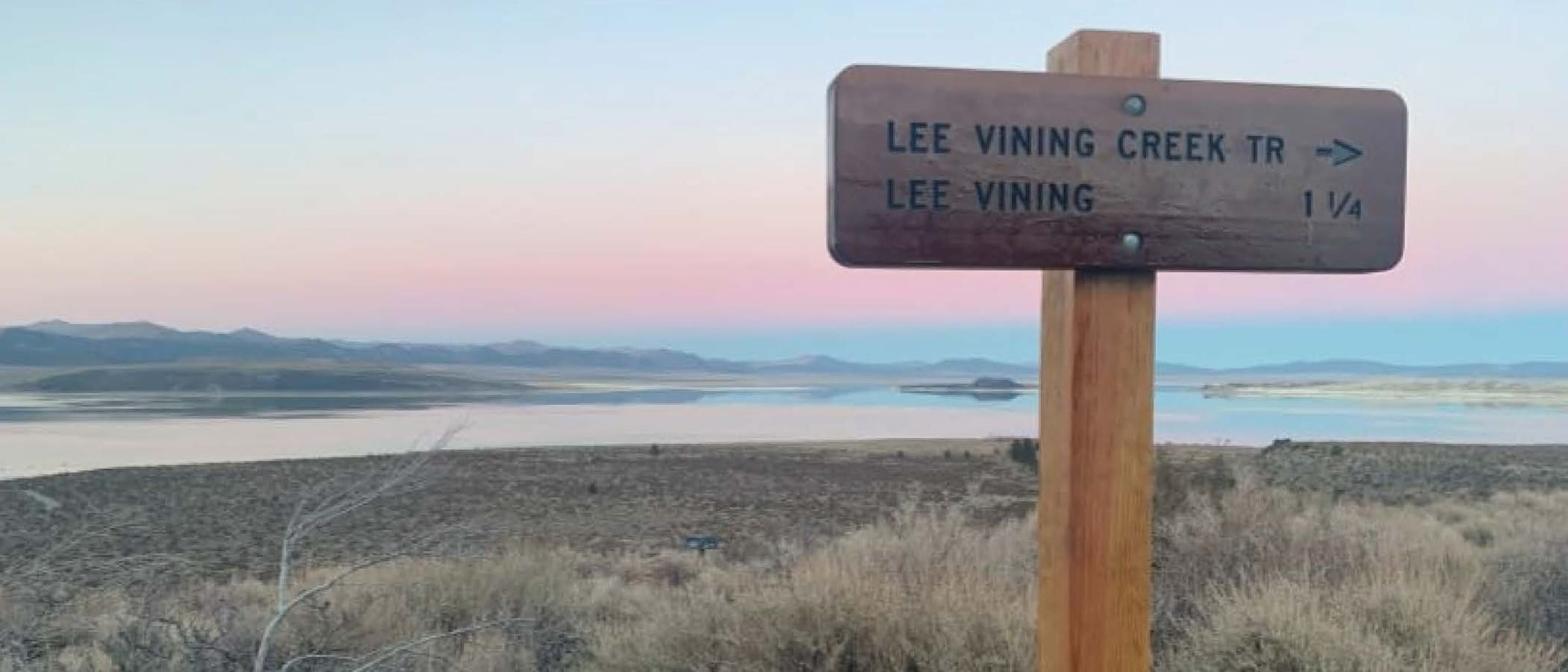A wooden trailhead for Lee Vining Creek stands against a sunset gradient of blur, yellow, and pink reflected in the Mono Lake water.