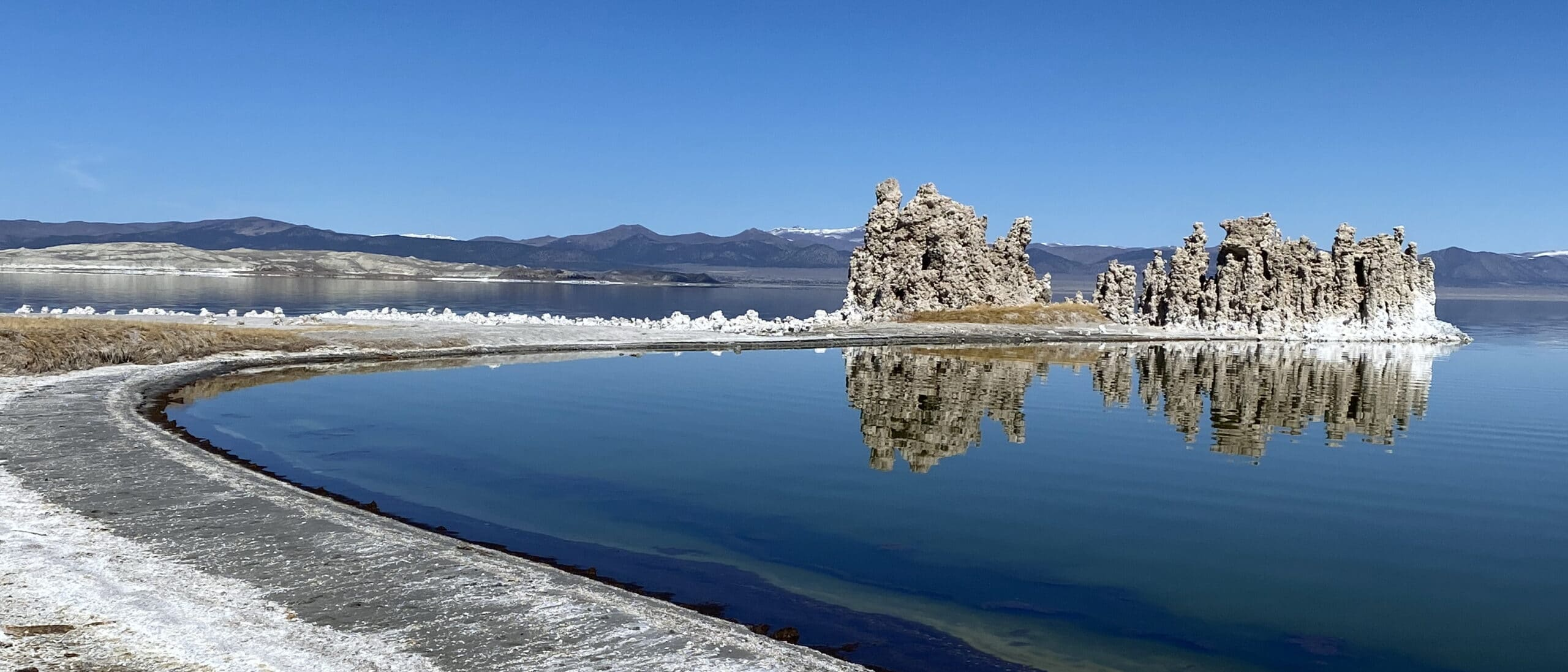 A white and grey shoreline wraps around to tufa towers perfectly reflected in a bright blue Mono Lake with clear blue skies above.
